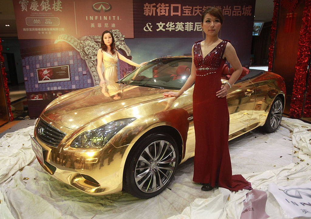 Models pose with a gold-plated Infiniti luxury sports car