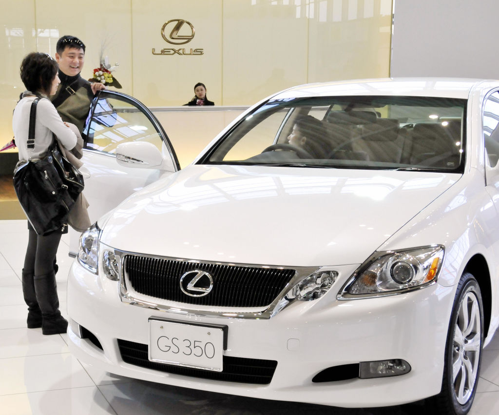 Customers check a Lexus vehicle at a Toyota showroom in Tokyo