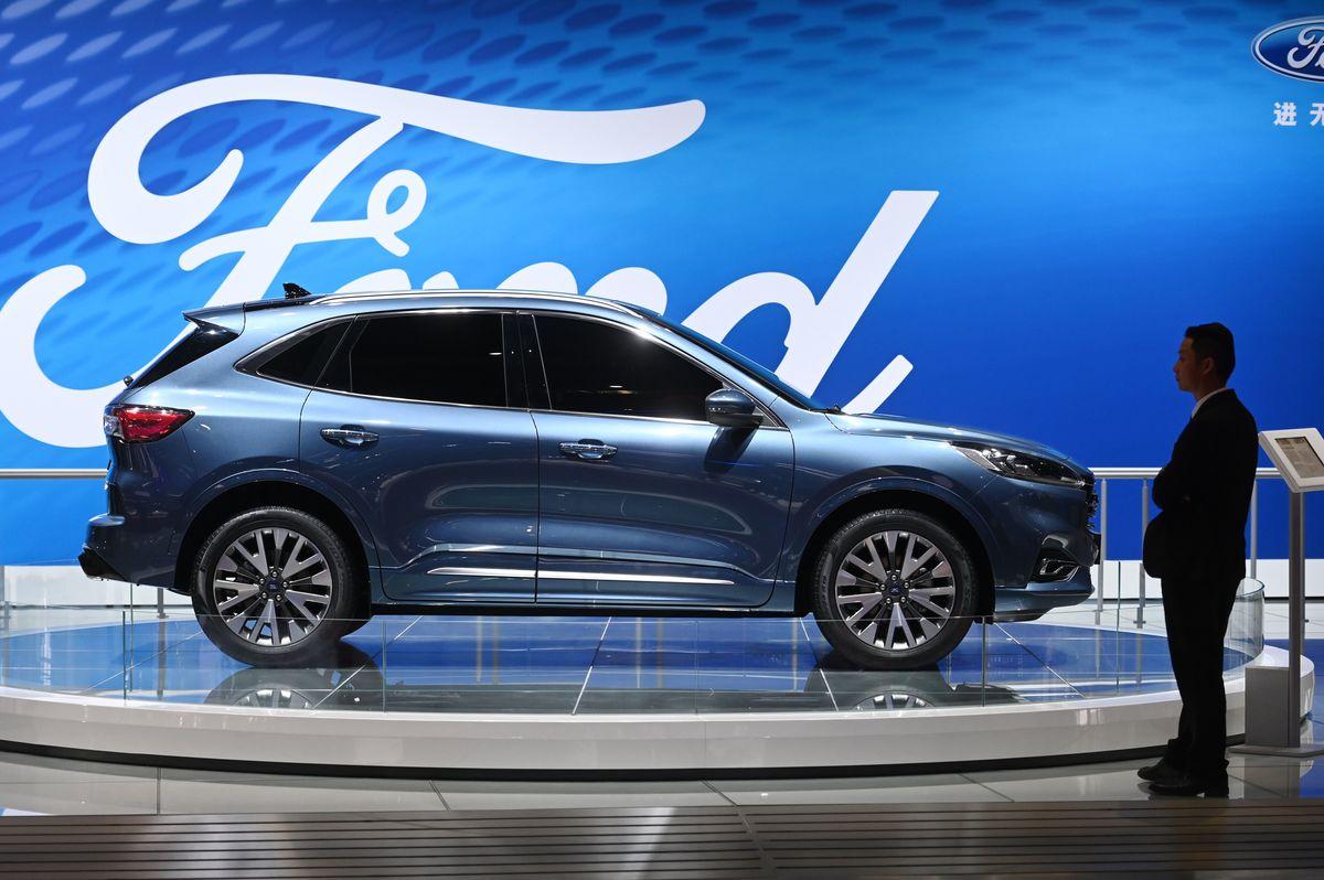A staff member stands beside a Ford Escape Titanium