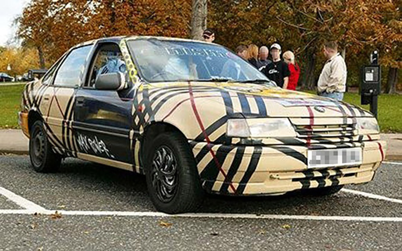 A car is covered in the Burberry company pattern.