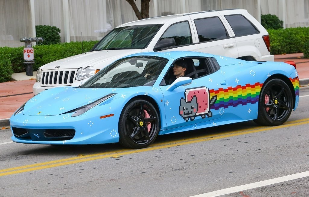 A sky blue Ferrari has a pixelated videogame cat and rainbow painted on its side.