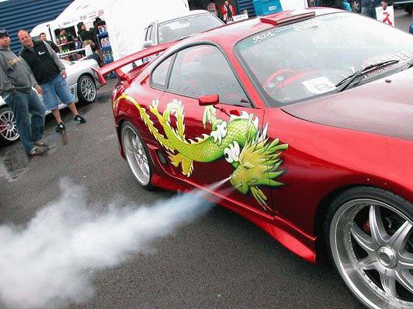 A red Toyota Supra has a green dragon painted on the side that blows out steam from its nostrils.