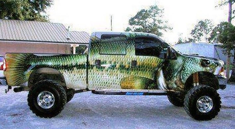 A large truck is covered with the image of a fish.