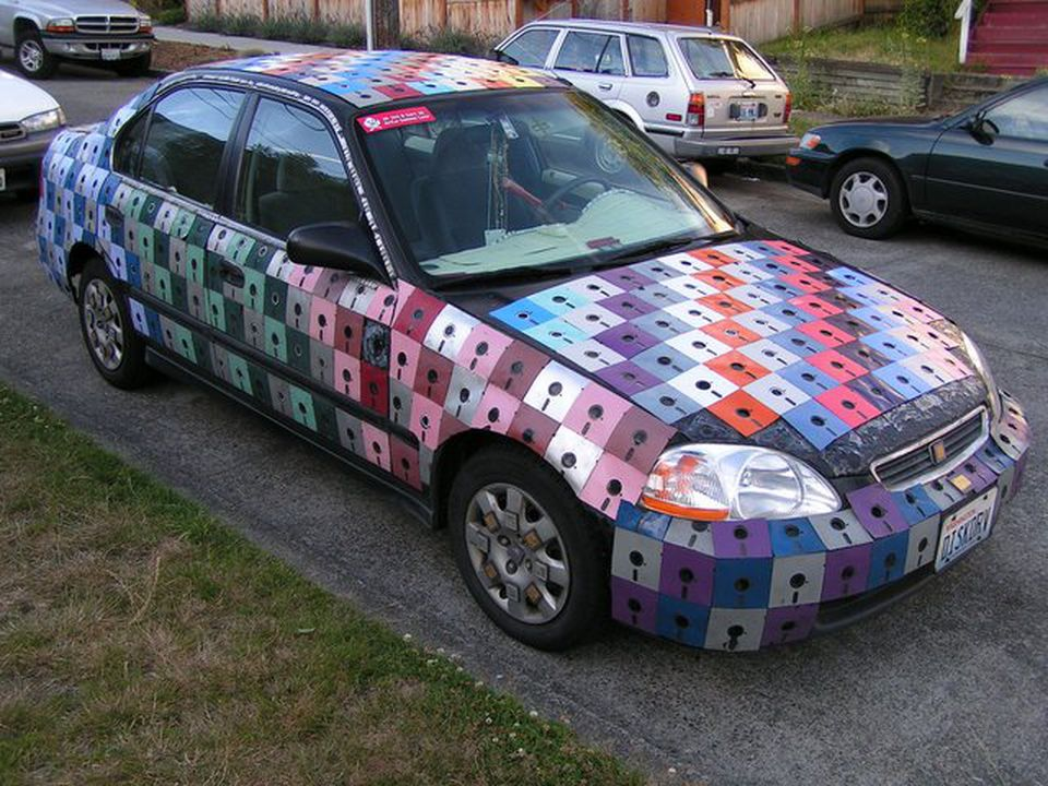 A car is covered in different colored floppy discs like a mosaic.