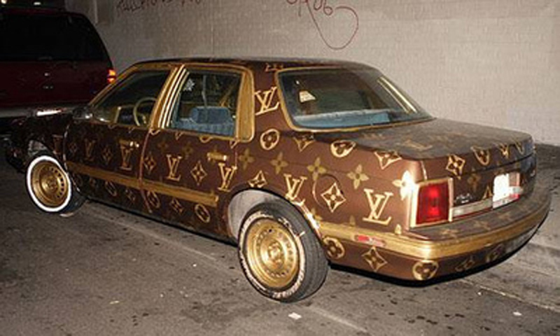 A car is covered in a gold and brown Louis Vuitton logo.