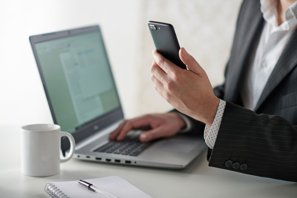 a businessman working at a desk with a smartphone and laptop