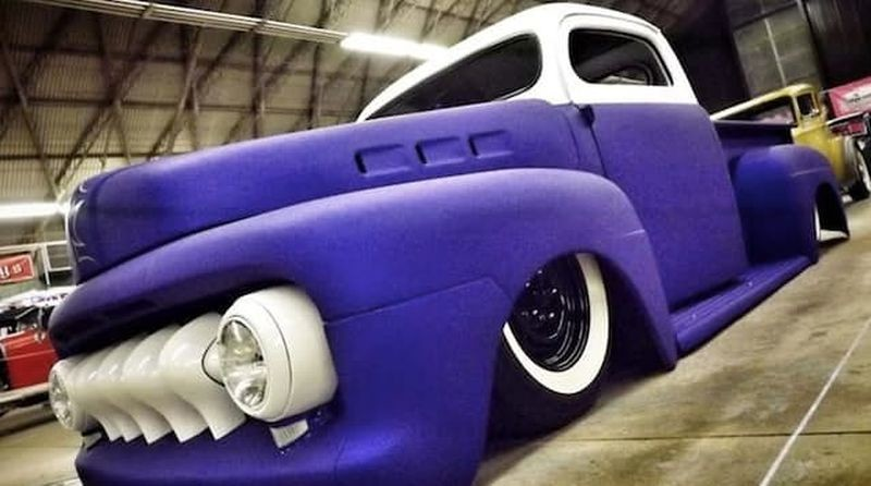 A restored pickup truck is white and purple.