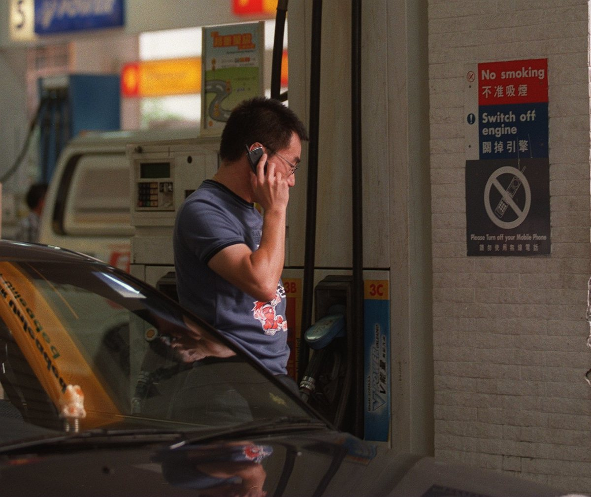 Man on the phone at a gas station