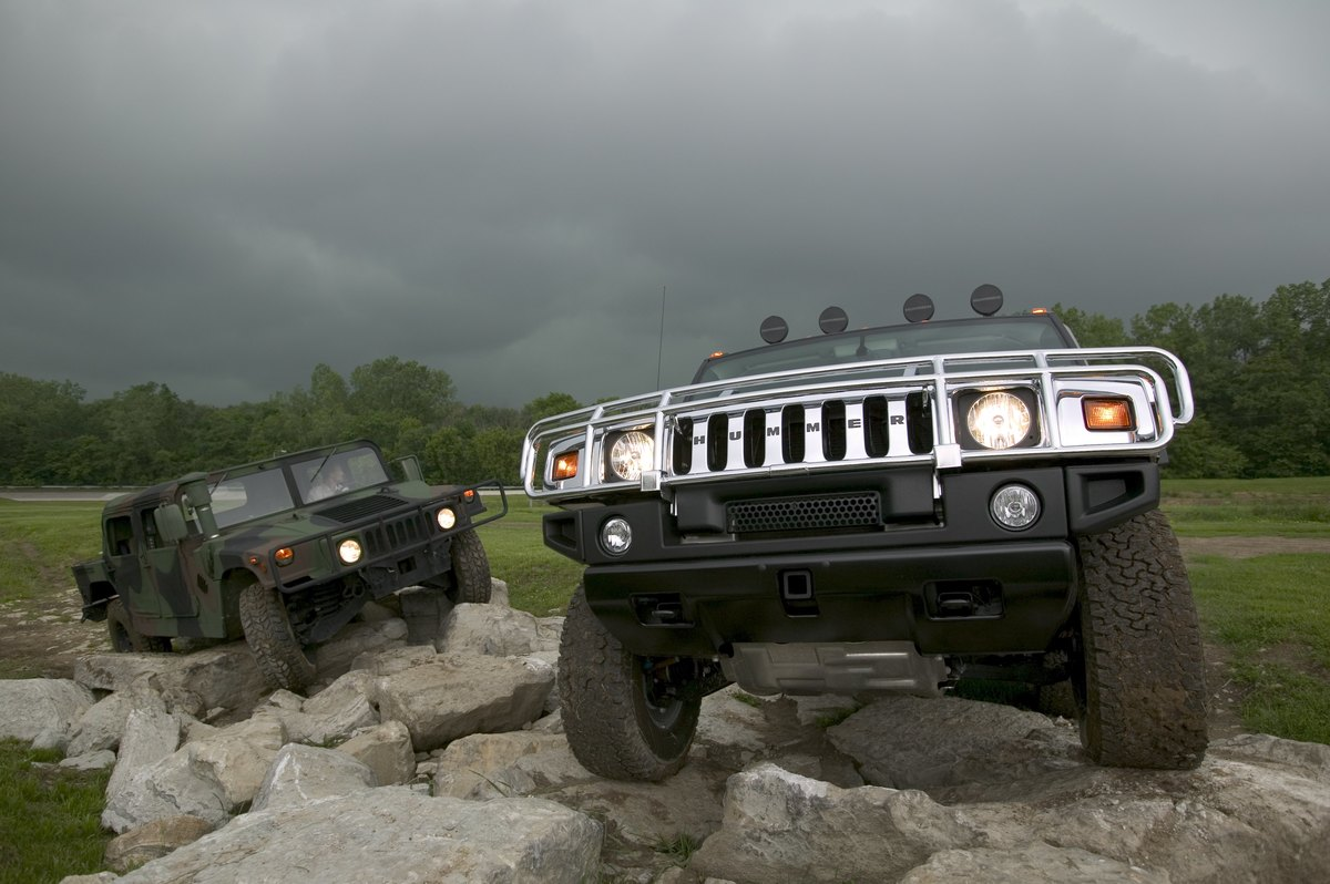 Hummer H2 Sport Utility Truck off roading over rocks with a military Humvee.