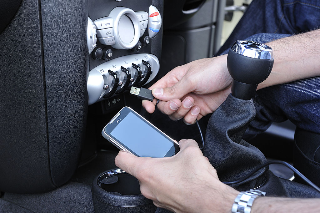 A mobile phone is plugged in to a car with a USB cable