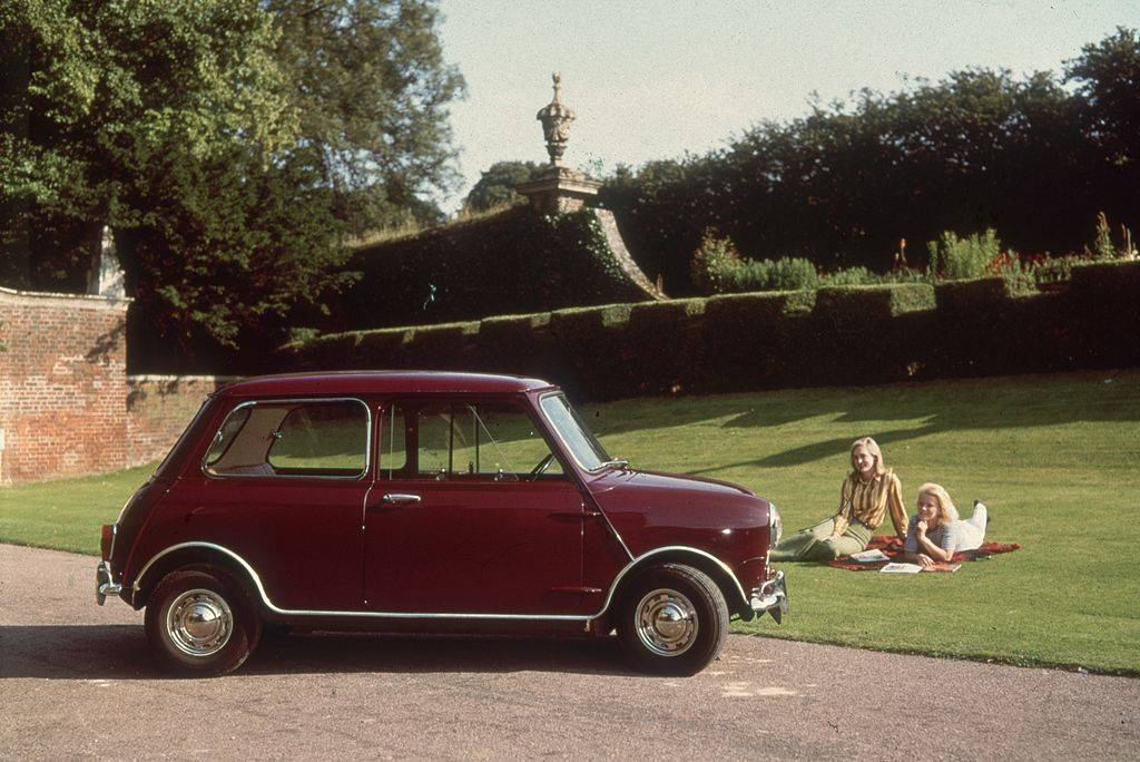 Two women relaxing on the lawn next to their Mini car.