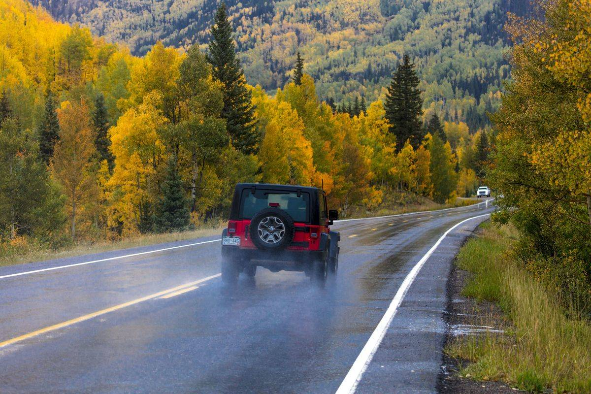 A jeep drives down a wet road in Colorado.