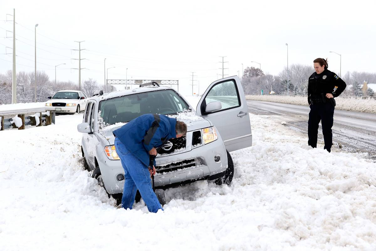 A man digs through his car on the side of a snowy highway in Kansas.