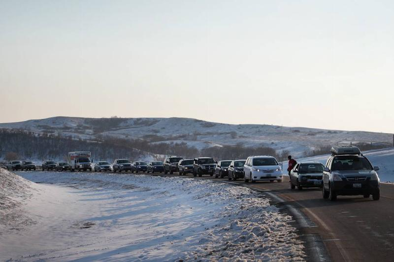 Cars drive by a snowy hill in North Dakota.