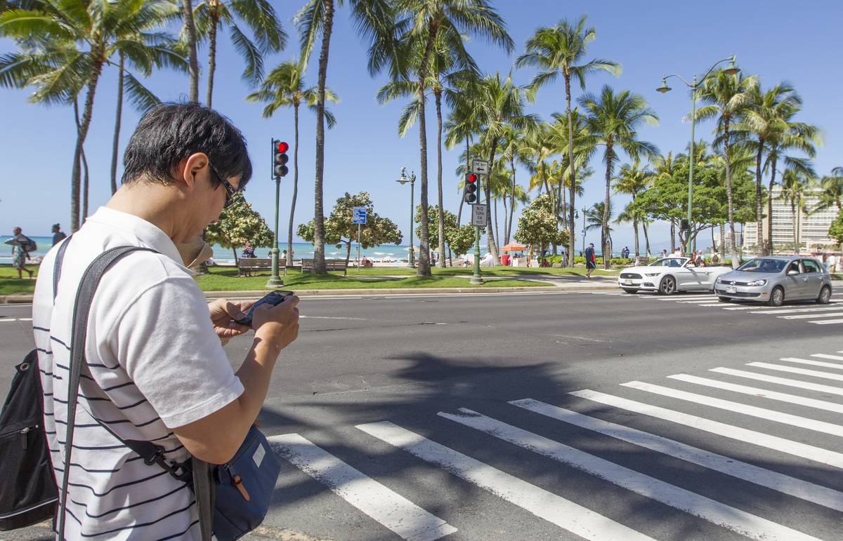 A man crosses the street while looking at his phone in Honolulu.