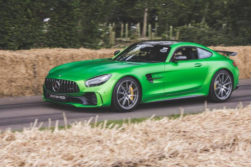 A green Mercedes-AMG GT drives down the road.