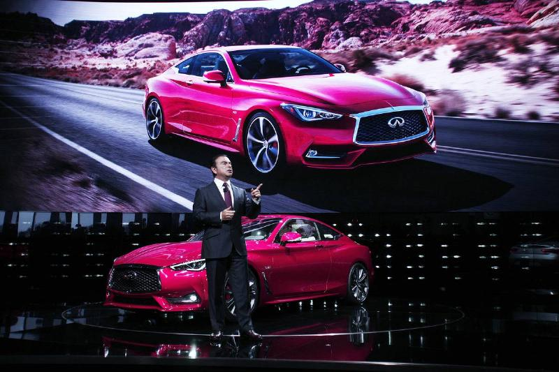 The CEO of Nissan shows the Infiniti Q60 in person and on a giant screen.