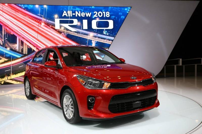 A 2018 Kia Rio is displayed beneath a sign.
