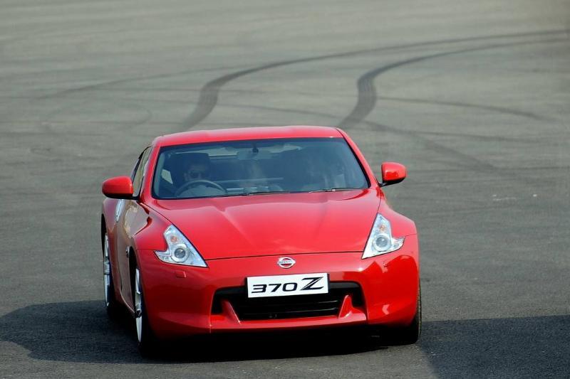 A red Nissan 370Z sports car drives across asphalt.