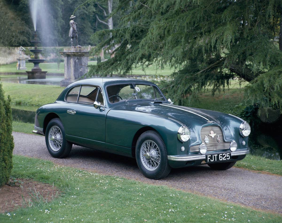 A 1952 Aston Martin DB2 saloon car photographed in a stately garden.
