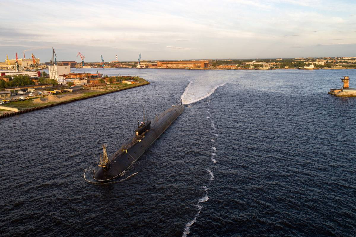 A Russian naval submarine glides across a bay.