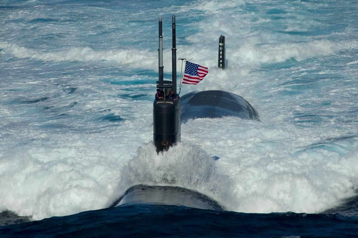 A Navy submarine with an American flag on top coasts across the ocean.