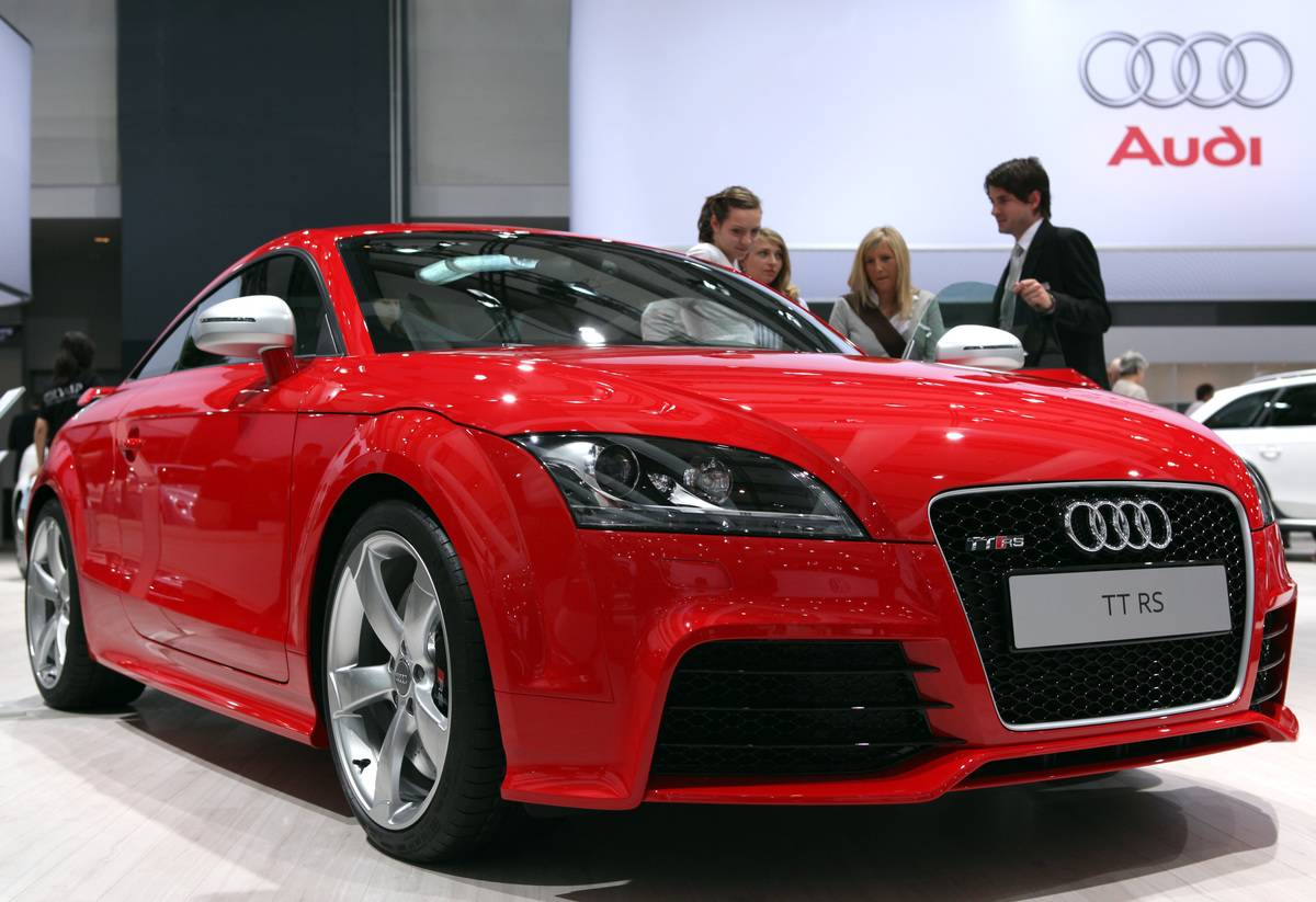 An employee shows visitors an Audi TT RS automobile at Volks