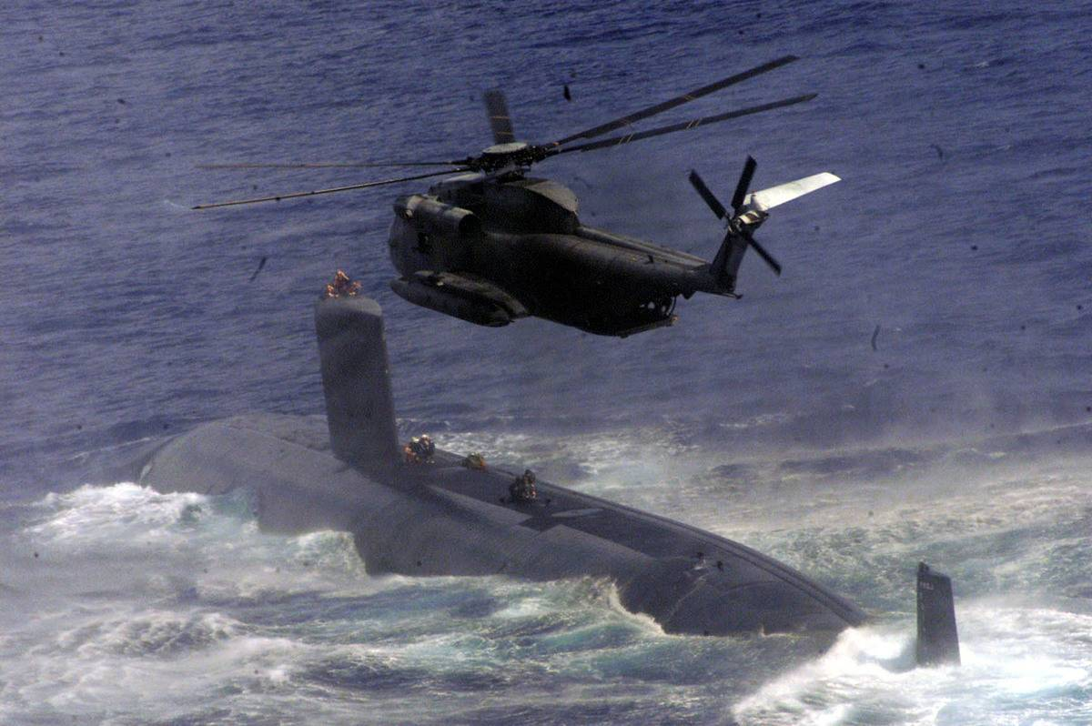 Navy Seals drop from a helicopter onto a submarine during joint training.