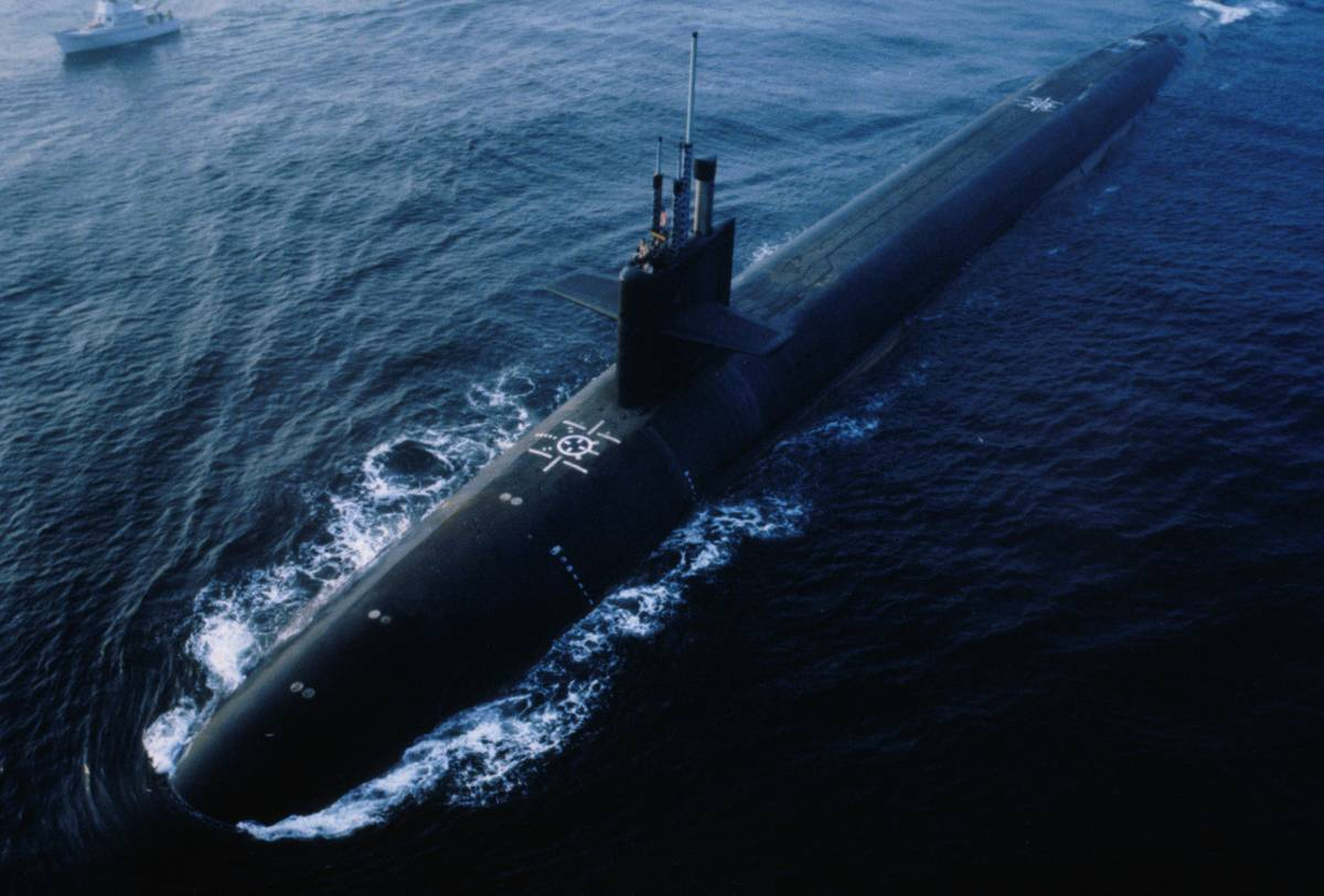 A full-length Ohio-class submarine is seen above the water.