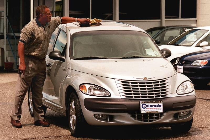 The new Chrysler PT Cruiser at Lithia Colo. Chrysler Plymouth dealership. Salesman Andy Dickerson wiping the rain drops from the roof.